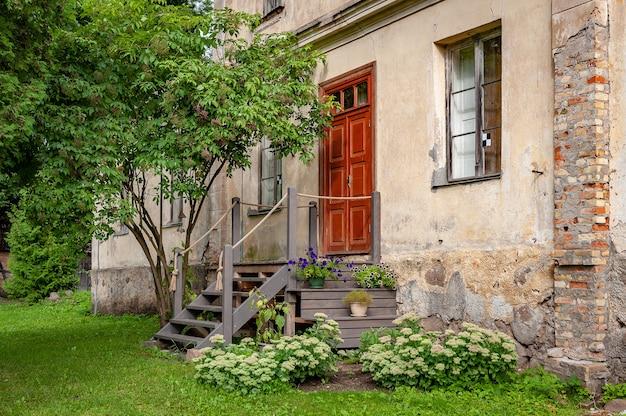 Vista del cortile della vecchia casa con gradini in legno e prato verde.