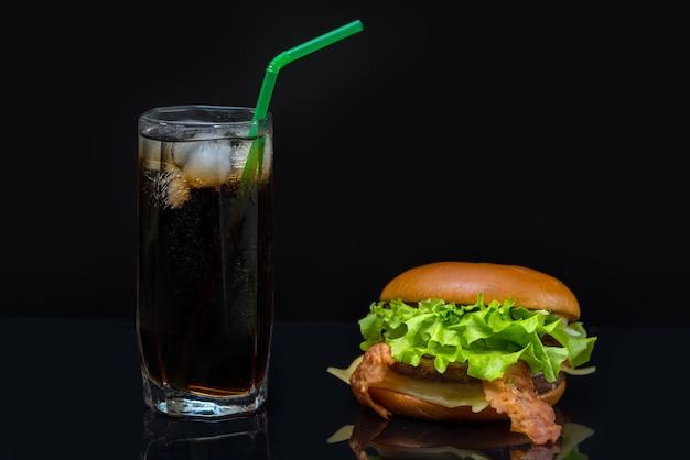 Hamburger di pancetta riempito con foglie di lattuga e un bicchiere di soda contenente ghiaccio seduto sul tavolo riflettente