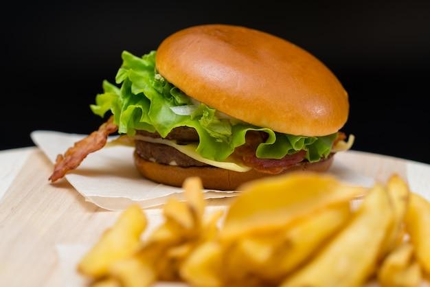 Cheeseburger con pancetta su un rotolo fresco croccante con patatine fritte su una tavola di legno con attenzione selettiva per l'hamburger