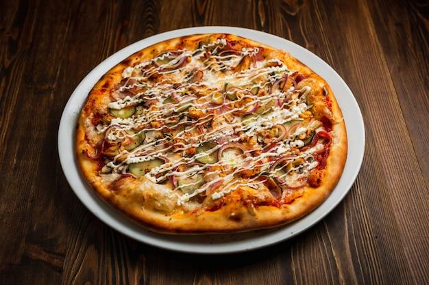 Pizza con pancetta, carne di pollo, funghi, cipolla, sottaceti e formaggio con salsa maionese, fondo in legno, scuro