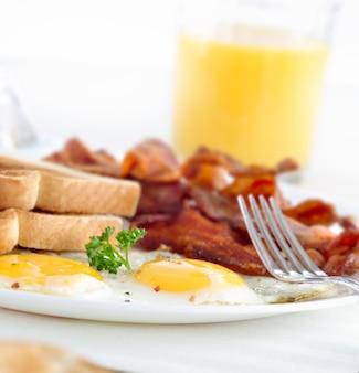 Colazione con pancetta, uova e pane tostato