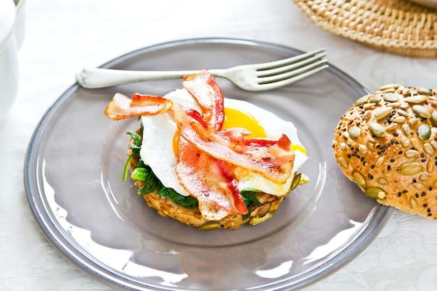 Uovo fritto pancetta e spinaci su sesamo semi di zucca brad