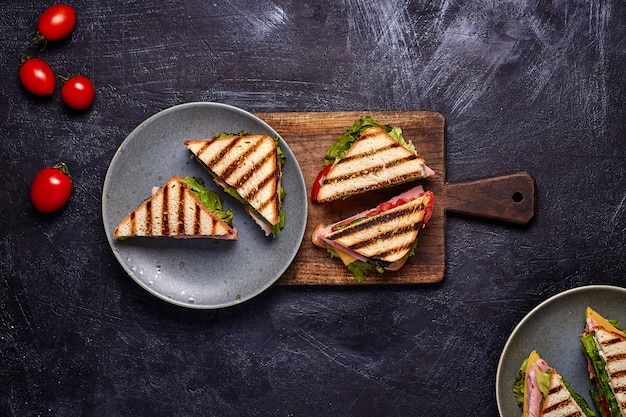 Primo piano del sandwitch del bacon con i pomodori freschi, le foglie dell'insalata della lattuga, il cetriolo ed il formaggio, sul fondo rustico concreto blu scuro della tavola, nessuno. vista dall'alto.