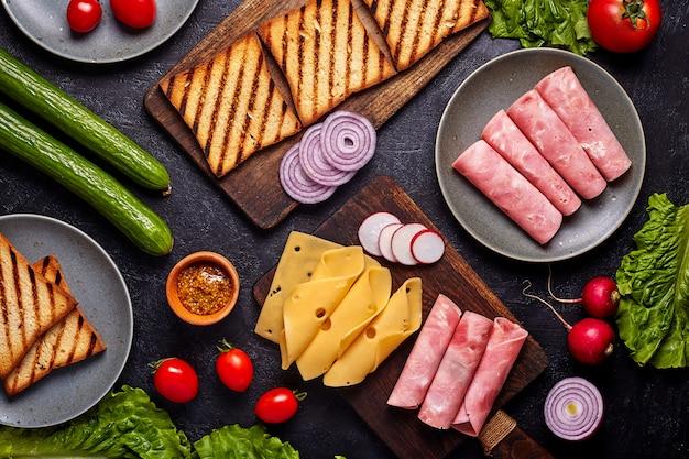 Primo piano del sandwitch del bacon con i pomodori freschi, le foglie dell'insalata della lattuga, il cetriolo ed il formaggio, sul fondo rustico concreto blu scuro della tavola, nessuno