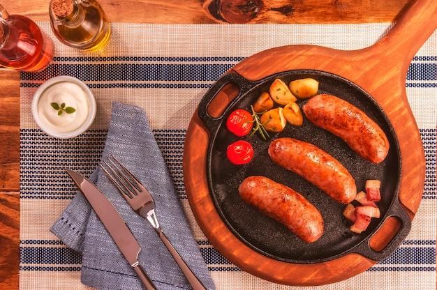 Salsiccia di pancetta arrostita in una padella di ferro