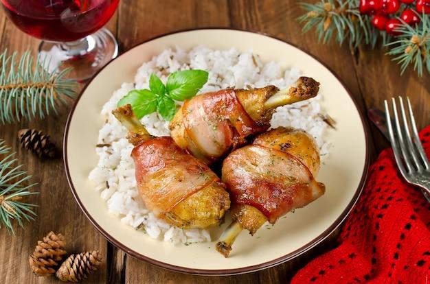 Cosce di pollo avvolte nella pancetta con contorno di riso. messa a fuoco selettiva