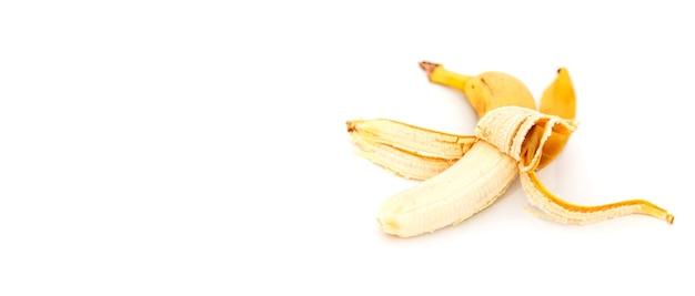 Banana difettosa isolata su fondo bianco. una vecchia banana sbucciata. frutto tropicale giallo. messa a fuoco selettiva. concetto di corretta alimentazione. posto per un'iscrizione o un logo