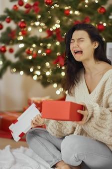 Cattivo regalo di natale donna delusa e infelice con la scatola regalo aperta al chiuso a casa