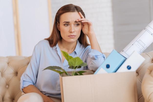 Brutta giornata. calma donna stanca senza lavoro seduta sul divano vicino a una grande scatola con documenti e pensa alla strana situazione che sta accadendo nella sua vita