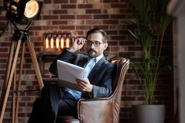 Cattiva vista. bel uomo adulto serio seduto in poltrona e tenendo gli occhiali durante la lettura dei suoi appunti