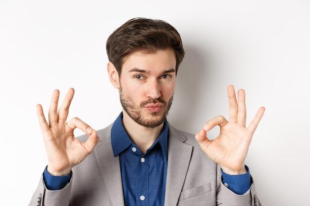 Non male. impressionato uomo d'affari caucasico annuisce in segno di approvazione, mostrando segni giusti per lodare e fare complimenti, sfondo bianco.