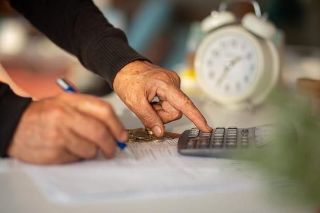 Cattivo investimento o crisi economica dal concetto di virus. mani dell'uomo anziano che contano le bollette, orologio sullo sfondo. attacco di crisi virale.
