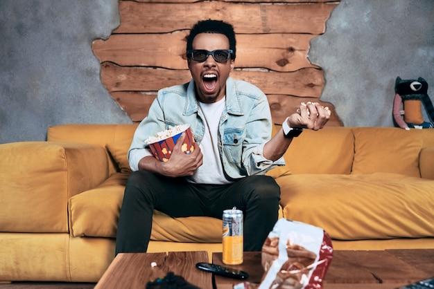 Film brutto. giovane arrabbiato in abbigliamento casual che mangia popcorn mentre guarda un film a casa