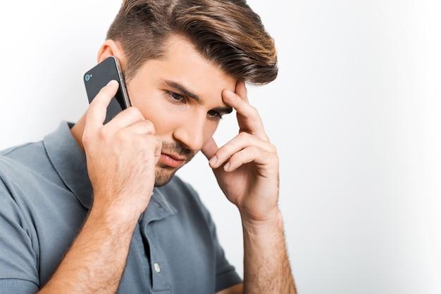 Cattive notizie. giovane depresso che parla al telefono cellulare e tocca il viso con la mano mentre si appoggia al muro