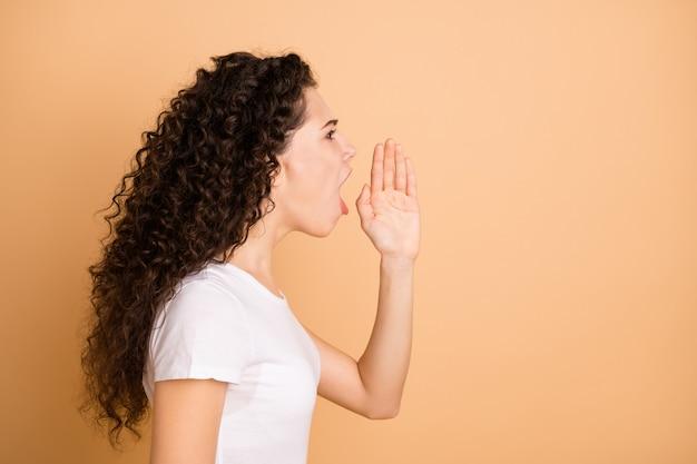 Brutte notizie ragazzi! foto del profilo di bella signora che urla forte rabbia allo spazio vuoto tenendo la mano vicino alla bocca indossare abbigliamento casual bianco isolato beige pastello colore di sfondo