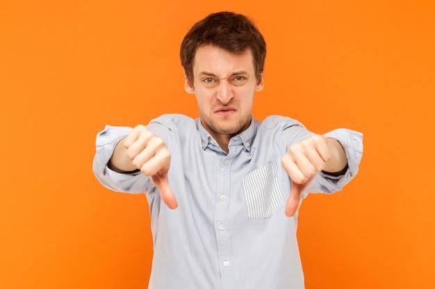 Uomo con un brutto segno che mostra antipatia alla telecamera e ha un aspetto triste