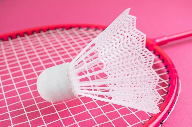 Racchetta da badminton e volano su un rosa brillante.