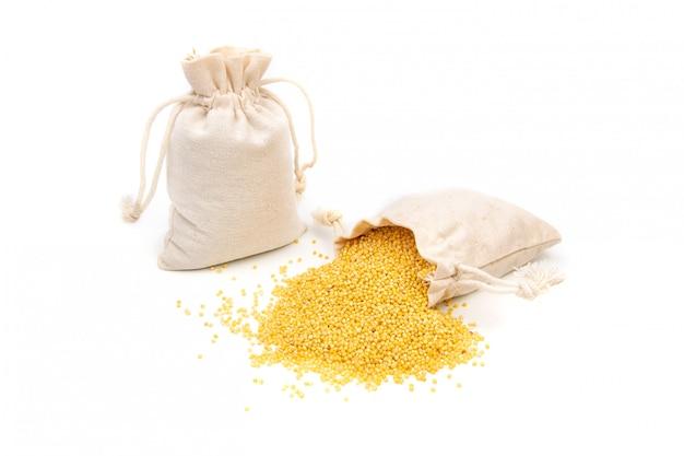 Borsa di miglio di cereali giallo su uno spazio bianco