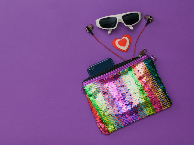 Borsa i colori dell'arcobaleno, smartphone, occhiali da sole e un cuore su uno sfondo viola. accessori moda per donna. lay piatto. la vista dall'alto.