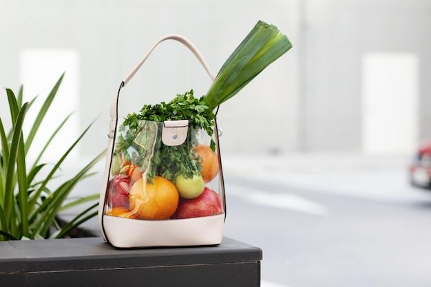 Un sacchetto di frutta e verdura fresca si trova su una panchina. bellezza, salute, stile di vita sano.