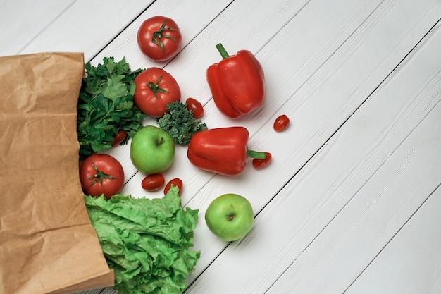 Sacchetto di verdure fresche su un tavolo di legno chiaro