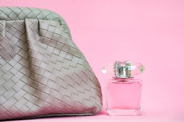 Borsa su sfondo rosa. borsa in pelle e bottiglia di profumo.