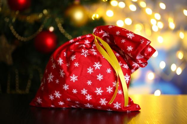 Borsa con regali sul tavolo su sfondo luminoso