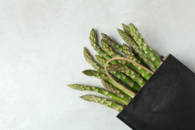 Borsa con asparagi verdi su sfondo bianco con texture