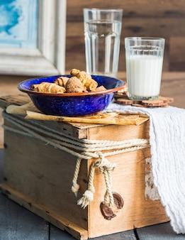 Biscotti bagel da una pasta frolla con ripieno, latte, nel piatto blu pasticceria dolce su un legno