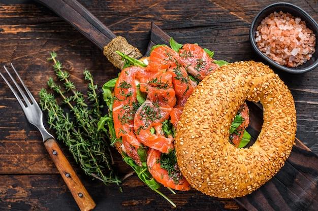 Sandwich di bagel con salmone e rucola. fondo in legno scuro. vista dall'alto.