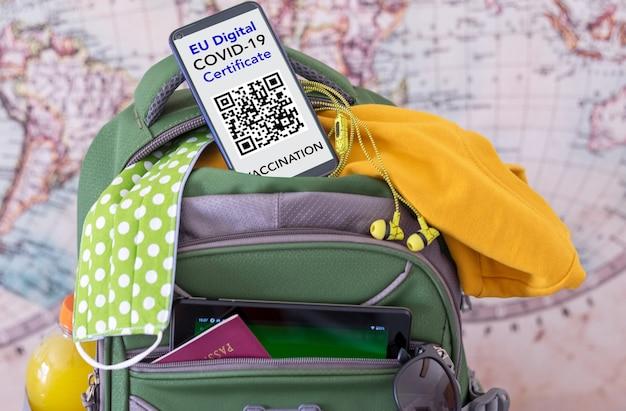 Bagaglio pronto per il viaggio, smartphone con certificato covid digitale europeo per persone vaccinate