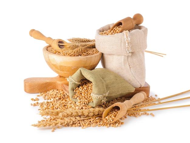 Borse e ciotola con chicchi di grano su sfondo bianco