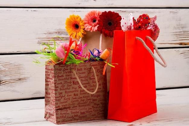 Sacchetti con fiori e caramelle sacchetti di carta gerbere fiocchi in tessuto preparano regali per tutta la giornata in famiglia...