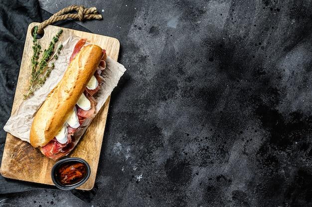 Panino baguette con prosciutto, formaggio camembert su un tagliere. sfondo nero, vista dall'alto, spazio per il testo