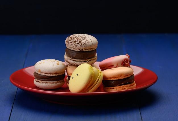 Macarons alle mandorle al forno su un piatto di ceramica rosso, sfondo blu