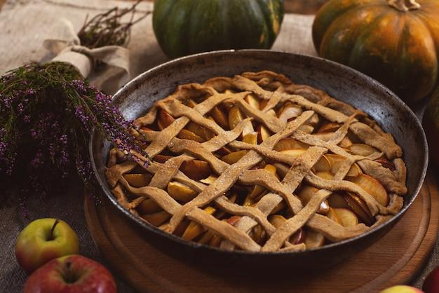 Torta di mele al forno in una teglia vicino alle zucche