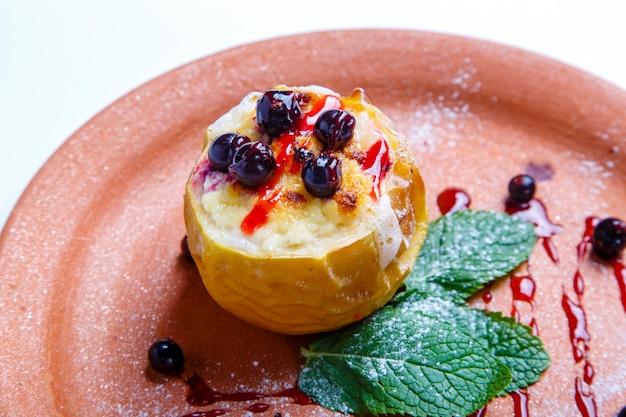 Mele al forno con mirtilli. un piatto di argilla. nelle vicinanze si trovano le foglie di menta. su uno sfondo bianco. avvicinamento