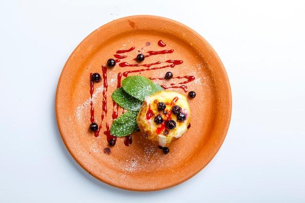 Mele al forno con mirtilli. un piatto di argilla. nelle vicinanze si trovano le foglie di menta. su uno sfondo bianco. vista dall'alto.