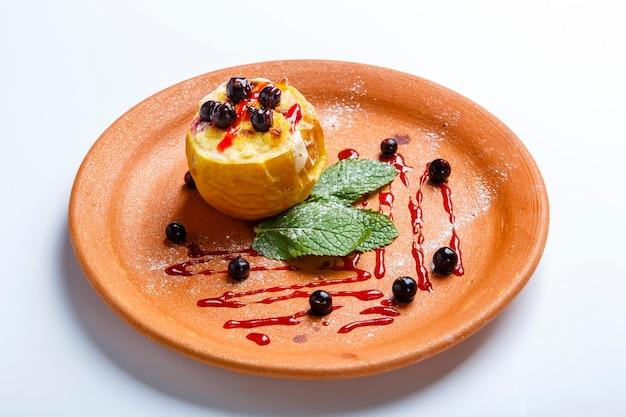 Mele al forno con mirtilli. un piatto di argilla. nelle vicinanze si trovano le foglie di menta. su uno sfondo bianco.