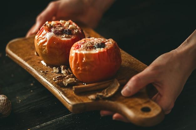 Mele al forno con ricotta con frutti di bosco e noci, condite con miele e cosparse di cannella. su una superficie di legno in stile rustico