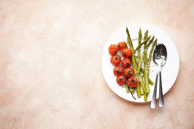 Asparagi al forno e pomodorini in un piatto su fondo beige, posto per il testo. vista dall'alto. Foto Premium