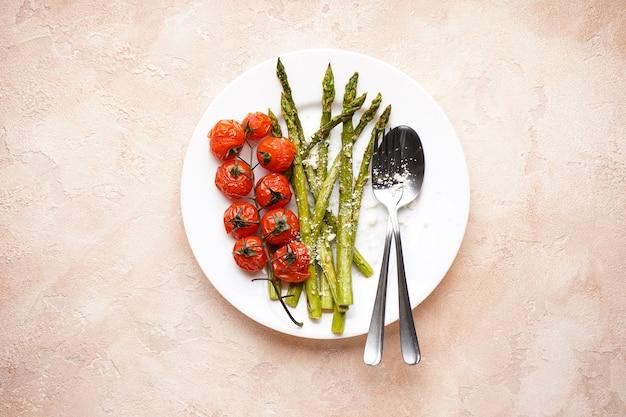 Asparagi al forno e pomodorini in un piatto su fondo beige. vista dall'alto.
