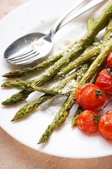 Asparagi al forno e pomodorini in un piatto su fondo beige, in verticale. avvicinamento.