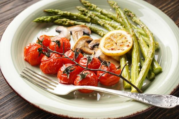Asparagi al forno con pomodorini e limone in un piatto su una superficie di legno, primo piano.