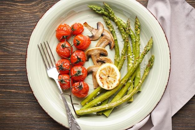 Asparagi al forno con pomodorini e limone in un piatto su una superficie di legno. lay piatto
