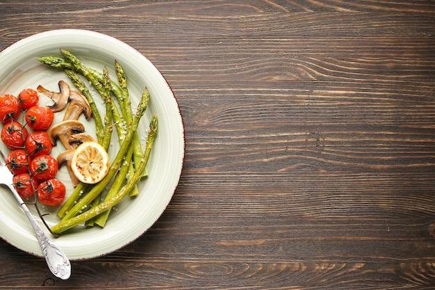 Asparagi al forno con pomodorini e limone in un piatto su una superficie di legno, spazio per il testo. vista dall'alto.