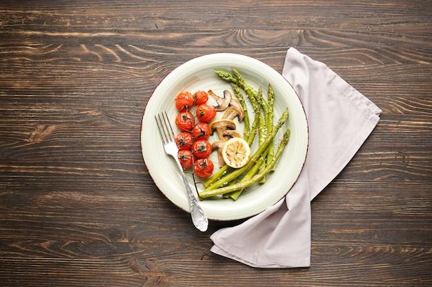Asparagi al forno con pomodorini e limone sulla piastra su una superficie di legno. vista dall'alto