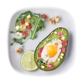 Crogiolo di avocado al forno con cubetti di prosciutto, uovo di quaglia e formaggio servito con insalata verde di rucola