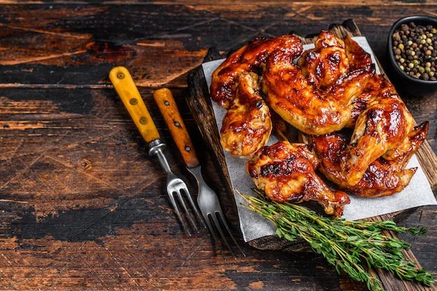 Ali di pollo al barbecue al forno con salsa dip. fondo in legno scuro. vista dall'alto. copia spazio.