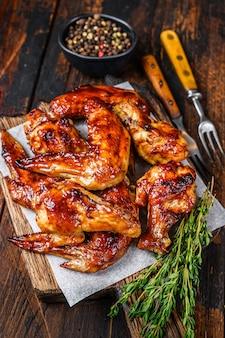 Ali di pollo al barbecue al forno con salsa dip. tavolo in legno scuro. vista dall'alto.